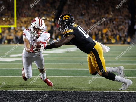 Wisconsin wide receiver Danny Davis, left, dives over the goal line for the touchdown despite defensive efforts by Iowa defensive back Michael Ojemudia, right, during the second half of an NCAA college football game, in Iowa City