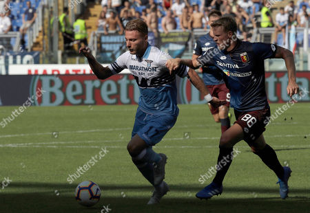 Lazio's Ciro Immobile, left, and Genoa's Oscar Hiljemark compete for the ball during a Serie A soccer match between Lazio and Genoa at Rome's Olympic stadium
