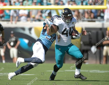 Jacksonville Jaguars running back Tommy Bohanon (40) is stopped by Tennessee Titans linebacker Harold Landry during the second half of an NFL football game, in Jacksonville, Fla