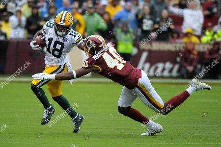 Green Bay Packers wide receiver Randall Cobb (left) runs the ball against Washington Redskins linebacker Josh Harvey-Clemons (right) during an NFL football game between the Green Bay Packers and Washington Redskins, in Landover, Md