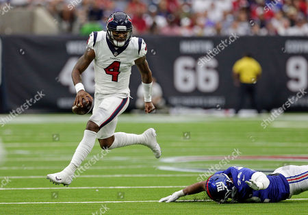 Houston Texans quarterback Deshaun Watson (4) breaks away from New York Giants defensive end Kerry Wynn (72) during the first half of an NFL football game, in Houston