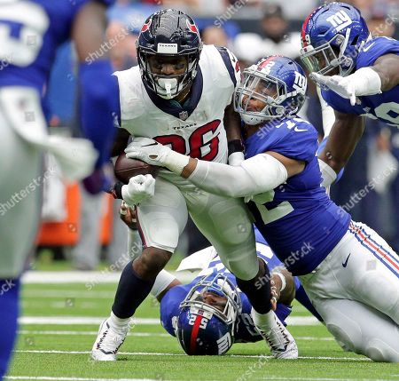 New York Giants defensive end Kerry Wynn (72) strips the ball away from Houston Texans running back Lamar Miller (26) during the second half of an NFL football game, in Houston. The Giants recovered the fumble