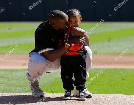 Kanye West, Saint West. Kanye West, kisses his son Saint after throwing out a ceremonial first pitch before a baseball game between the Chicago Cubs and the Chicago White Sox, in Chicago
