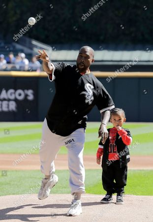 Kanye West, Saint West. Kanye West, left, throws out a ceremonial first pitch as his son Saint watches before a baseball game between the Chicago Cubs and the Chicago White Sox, in Chicago