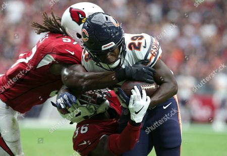 Chicago Bears running back Tarik Cohen (29) is tackled by Arizona Cardinals linebacker Josh Bynes (57) and safety Budda Baker (36) during the first half of an NFL football game, in Glendale, Ariz
