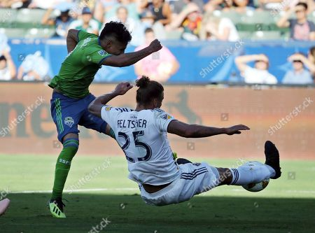 Seattle Sounders forward Raul Ruidiaz, left, and LA Galaxy defender Rolf Feltscher (25) tangle in the first half of an MLS soccer match in Carson, Calif., . The Galaxy won 3-0