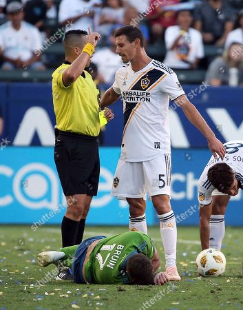 LA Galaxy defender Daniel Steres (5) discusses a foul call with a referee as Seattle Sounders forward Will Bruin (17) lies below in the second half of an MLS soccer match in Carson, Calif., . The Galaxy won 3-0