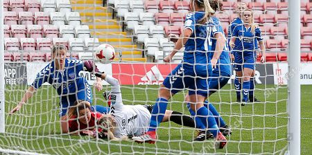 Goalkeeper Hannah Reid of Durham manages to divert the ball from goal even when floored