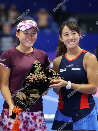 Japanese pair Miyu Kato (R) and Makoto Ninomiya (L) smile as they receive the trophy of the doubles of the Toray Pan Pacific Open tennis tournament in Tokyo. Japanese pair defeated Czech pair of Andrea Hlavackova and Barbora Strycova in the final 6-4, 6-4.