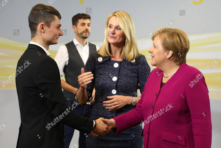 German Chancellor Angela Merkel (R) and the chief human resources manager of tire maker Continental, Ariane Reinhart (C), greet a participant of the  discussion meeting 'Sprechen wir ueber Europa' ('Let's talk about Europe') in Hannover, northern Germany, 24 September 2018. Merkel meets young adults  at the headquarters of Continental.