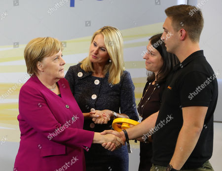 Stock Image of German Chancellor Angela Merkel (L) and the chief human resources manager of tire maker Continental, Ariane Reinhart (2-L), greet  participants of the  discussion meeting 'Sprechen wir ueber Europa' ('Let's talk about Europe') in Hannover, northern Germany, 24 September 2018. Merkel meets young adults  at the headquarters of Continental.