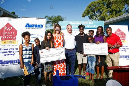 Aaron's, Inc., a leading omnichannel provider of lease-purchase solutions, and its divisions Aaron's and Progressive Leasing, surprised two single mothers and their children today with rooms of furniture to fill their new homes as part of Homes for the Holidays (HFTH) program sponsored by former NFL star Warrick Dunn, on in Tampa, Fla. The 162nd and 163rd homes were presented by Warrick Dunn Charities' (WDC) HFTH program, which assists single parents in becoming first-time homeowners by providing the materials necessary for long-term stability and the provisions required to ensure that both parent and children can thrive educationally, socially and economically