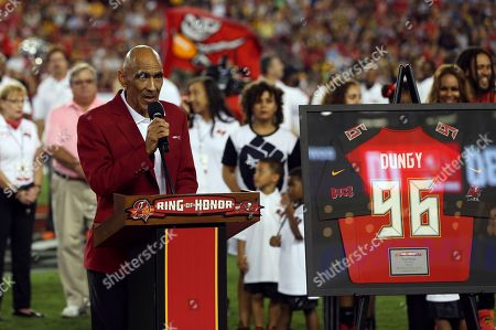 Stock Image of Former Tampa Bay Buccaneers head coach Tony Dungy speaks to the fans after being inducted in the team's Ring of Honor during halftime of an NFL football game against the Pittsburgh Steelers, in Tampa, Fla