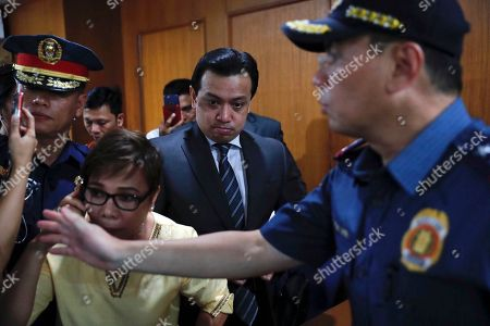 Philippine Senator Antonio Trillanes IV (C), a former military mutiny leader, is escorted in a trial court building as he posts bail for an arrest warrant in Makati City, south of Manila, Philippines, 25 September 2018. A Makati City regional trial court issued an arrest warrant for Trillanes on 25 September, in relation to rebellion charges against him during the term of former President Gloria Macapagal-Arroyo. Philippine President Rodrigo Duterte, through a proclamation signed on 31 August, revoked the amnesty granted to Trillanes in relation to his involvement in military uprisings against former President Macapagal-Arroyo.