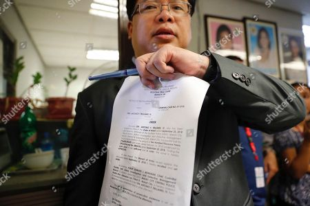 Filipino lawyer Rey Robles, representing Philippine Senator Antonio Trillanes IV (not in photo), shows documents on Trillanes' bail for an arrest warrant in Makati City, south of Manila, Philippines, 25 September 2018. A Makati City regional trial court issued an arrest warrant for Trillanes on 25 September, in relation to rebellion charges against him during the term of former President Gloria Macapagal-Arroyo. Philippine President Rodrigo Duterte, through a proclamation signed on 31 August, revoked the amnesty granted to Trillanes in relation to his involvement in military uprisings against former President Macapagal-Arroyo.