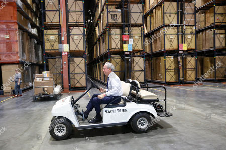 City Furniture CEO Keith Koenig, rides through his wear house after an interview with the Associated Press, in Tamarac, Fla. Koenig and inventor Charles Hall, pioneers of the waterbed industry in the United States, are hoping to generate a new wave of popularity for the old furniture concept by using a wholesome new pitch