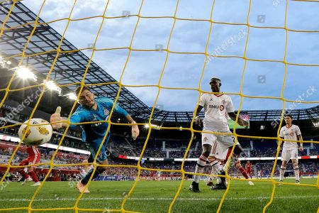 Toronto FC goalkeeper Alex Bono, left, dives but is unable to stop a scoring shot by New York Red Bulls midfielder Alejandro Romero Gamarra, back left, during the second half of a soccer game, in Harrison, N.J. The Red Bulls won 2-0