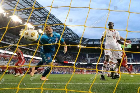 Toronto FC goalkeeper Alex Bono, left, dives but is unable to stop a scoring shot by New York Red Bulls midfielder Alejandro Romero Gamarra, far left, during the second half of a soccer game, in Harrison, N.J. The Red Bulls won 2-0