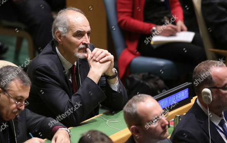 Syria's United Nations Ambassador Bashar Jaafari, center, listens as President Donald Trump address the United Nations General Assembly, at U.N. headquarters