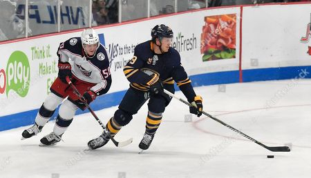 Stock Photo of Buffalo Sabres defenseman Jake McCabe, right, skates the puck away from Columbus Blue Jackets left wing Eric Robinson during the second period of an NHL preseason hockey game in Clinton, N.Y