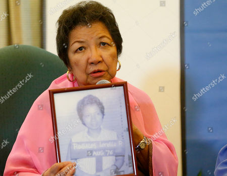 """Loretta Anne Rosales. Former human rights chair and martial law victim Loretta Rosales shows a mugshot of her when she was arrested during the martial law period as she relates her ordeal while in detention at a foreign correspondents forum, in Manila, Philippines. The forum was in response to the recent one-on-one interview by Ferdinand """"Bongbong"""" Marcos Jr., the son of the late dictator Ferdinand Marcos, with former Senate President Juan Ponce Enrile, the so-called architect of martial law when Enrile challenged anyone to name one person who got arrested simply because he or she criticized former President Ferdinand Marcos"""