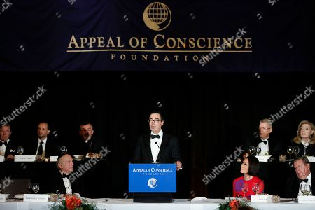 Stock Picture of United States Treasury Secretary Steven T. Mnuchin delivers the keynote address as Rabbi Arthur Schneier, left, president and founder of the Appeal of Conscience Foundation, lots on during the 2018 Appeal of Conscience Gala at the Grand Hyatt New York, in New York