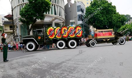 An army officer salutes as national flag-draped coffin of late President Tran Dai Quang on truck-drawn artillery carriage passes by in Hanoi, Vietnam, . Thousands of people line streets in capital Hanoi to pay their last respects to the late president who died last week of viral illness