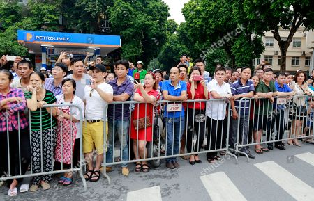 Hanoi residents line a street in Hanoi, Vietnam to pay last respect to late President Tran Dai Quang who died last week of viral illness. Some were using smart phones to catch images of his flag-draped coffin on truck-drawn artillery carriage