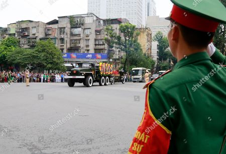 An solider salutes as national flag-draped coffin of late President Tran Dai Quang on truck-drawn artillery carriage passes by in Hanoi, Vietnam, . Thousands of people line streets in capital Hanoi to pay their last respects to the late president who died last week of viral illness