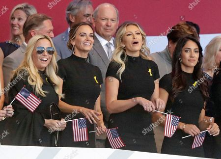 Amy Mickelson, the wife of Phil Mickelson of the US, Jena Sims the partner of Brooks Koepka, Paulina Gretzky, the partner of Dustin Johnson and Allison Stokke the partner of Rickie Fowler, from left, take their seats for the opening ceremony of the Ryder Cup at Le Golf National in Saint-Quentin-en-Yvelines, outside Paris, France, . The 42nd Ryder Cup will be held in France from Sept. 28-30, 2018 at Le Golf National