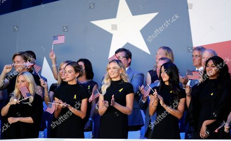 US team's wives and partners wave their national flags during the opening ceremony of the Ryder Cup at Le Golf National in Saint-Quentin-en-Yvelines, outside Paris, France, . Jena Sims, left, Amy Mickelson, 2nd left, and Paulina Gretzky, 2nd right, The 42nd Ryder Cup will be held in France from Sept. 28-30, 2018 at Le Golf National