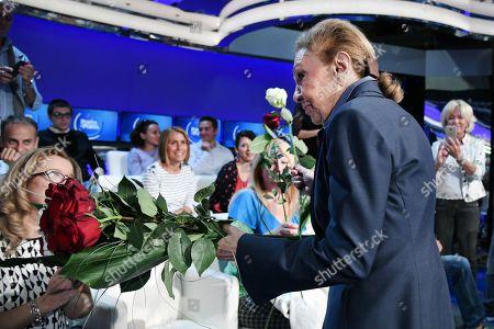 Empress Farah Pahlavi born Farah Diba widow of Mohammad Reza Pahlavi Shah of Iran, gives roses to women in the audience