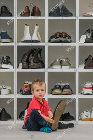Emlyn Simmonds (age 2.5) tries the shoes for size - Bedwyr Williams' Walk A Mile In My Shoes, a display case with 45 pairs of his own size 13 shoes. He invites the audience to share in his own 'problems of ' by trying them on