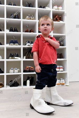 "Stock Image of Emlyn Simmonds, aged two and a half, from Lewisham, wears a pair of size 13 shoes, in front of an installation called ""Walk A Mile In My Shoes"", 2006, by Bedwyr Williams  Preview of ""Black Mirror"", a major new exhibition featuring the work of 26 contemporary artists, at the Saatchi Gallery."