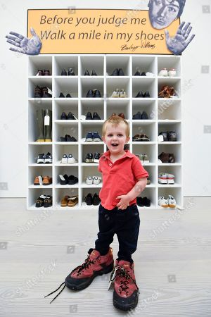 "Emlyn Simmonds, aged two and a half, from Lewisham, wears a pair of size 13 shoes, in front of an installation called ""Walk A Mile In My Shoes"", 2006, by Bedwyr Williams  Preview of ""Black Mirror"", a major new exhibition featuring the work of 26 contemporary artists, at the Saatchi Gallery."