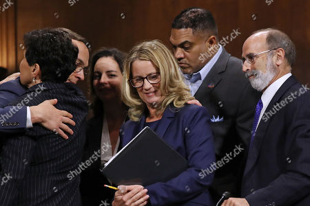 Christine Blasey Ford (C) is surrounded by her attorney Michael Bromwich (R), supporters and security agents after she testified before the Senate Judiciary Committee in the Dirksen Senate Office Building. A professor at Palo Alto University and a research psychologist at the Stanford University School of Medicine, Ford has accused Supreme Court nominee Judge Brett Kavanaugh of sexually assaulting her during a party in 1982 when they were high school students in suburban Maryland.