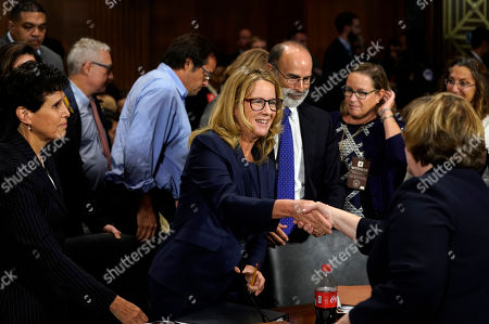 Christine Blasey Ford shakes hands with Phoenix prosecutor Rachel Mitchell as she finished testifying before the Senate Judiciary Committee on Capitol Hill