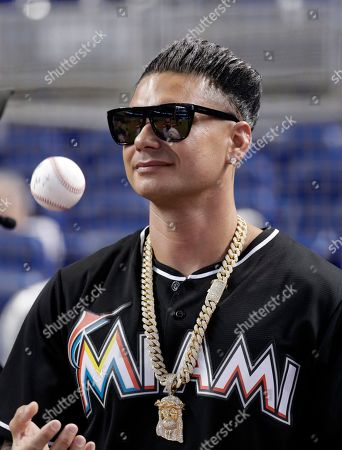 DJ Pauly D waits to throw a ceremonial pitch before a baseball game between the Miami Marlins and Atlanta Braves, in Miami
