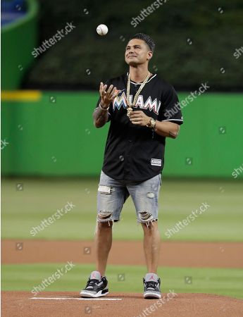 DJ Pauly D prepares to throw a ceremonial pitch before a baseball game between the Miami Marlins and Atlanta Braves, in Miami