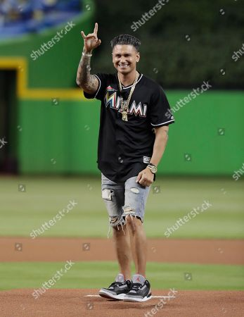 DJ Pauly D gestures after throwing a ceremonial pitch before a baseball game between the Miami Marlins and Atlanta Braves, in Miami