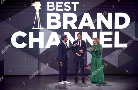 Martell Beck (C), marketing chief of 'BVG' receives his Golden Camera trophy in the category 'Best Brand Channel' from hosts Steven Gaetjen (L) and Jeannine Michaelsen (R) during the 'YouTube Goldene Kamera Digital Award 2018' ceremony in Berlin, Germany, 27 September 2018. The best German web video producers in eight categories will be awarded at the event.