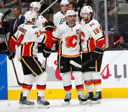 Calgary Flames left wing James Neal (18) is congratulated by teammates Travis Hamonic (24) and Mark Giordano (5) after scoring a goal against the San Jose Sharks during the second period of a preseason NHL hockey game in San Jose, Calif., on