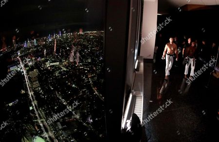 Jorge Perez, right, of the Dominican Republic, walks with Spyros Margaritopoulos, of Greece, before their 84-kilogram bout during a Karate Combat fight on the observation deck of the World Trade Center, in New York. The city is seen through a window at left