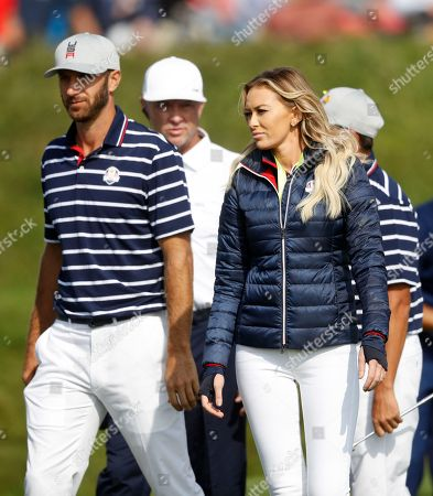 Dustin Johnson of the US, left, walks with his partner Paulina Gretzky on 16th green at the end of a fourball match on the opening day of the 42nd Ryder Cup at Le Golf National in Saint-Quentin-en-Yvelines, outside Paris, France, . Johnson and Fowler won 4 and 2 over Europe's Rory McIlroy and Thorbjorn Olesen