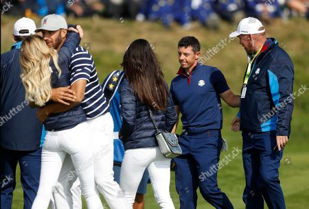 Dustin Johnson of the US, second left, is embraced by his partner Paulina Gretzky on 16th green as Europe's Rory McIlroy is greeted by Europe team captain Thomas Bjorn, right, at the end of a fourball match on the opening day of the 42nd Ryder Cup at Le Golf National in Saint-Quentin-en-Yvelines, outside Paris, France, . Johnson and Rickie Fowler won 4 and 2 over Europe's Rory McIlroy and Thorbjorn Olesen