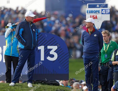 Europe team captain Thomas Bjorn, left, talks to Europe team vice-captain Robert Karlsson during a foursome match on the opening day of the 42nd Ryder Cup at Le Golf National in Saint-Quentin-en-Yvelines, outside Paris, France
