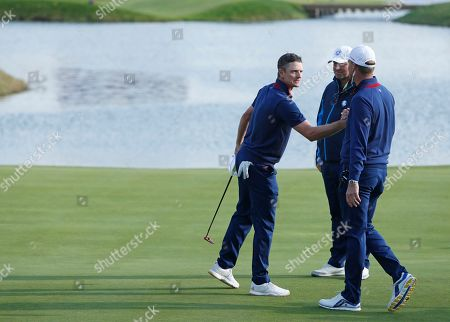 Europe's Justin Rose, left, is greeted by Europe team captain Thomas Bjorn, center, and Europe team vice-captain Robert Karlsson after winning a foursome match on the opening day of the 42nd Ryder Cup at Le Golf National in Saint-Quentin-en-Yvelines, outside Paris, France, . Rose and Stenson beat Dustin Johnson of the US and Rickie Fowler 3 and 2
