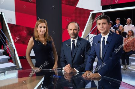 French journalists Lea Salame (L) and Thomas Sotto (R) pose with French Prime Minister Edouard Philippe