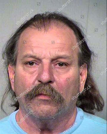 This undated photo provided by the Maricopa County Sheriff's Office shows 59-year-old Charles Eugene Robbins of Phoenix, who was booked, on suspicion of murder in the 2014 ax-bludgeoning death of 40-year-old Joshua C. Calkins in Phoenix. Robbins is the second man to be charged with murder in Calkins' death. Christopher Paul Mason was charged nearly four years ago with murder and other charges in Calkins' death