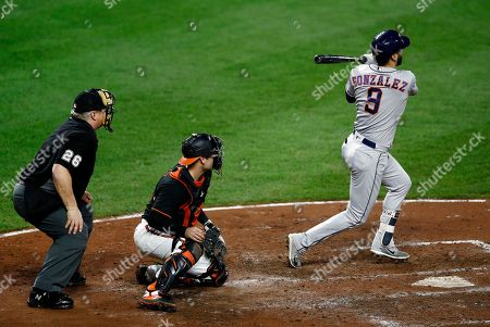 Marwin Gonzalez, Austin Wynns, Bill Miller. Houston Astros' Marwin Gonzalez, right, singles in front of Baltimore Orioles catcher Austin Wynns, center, and umpire Bill Miller, left, in the eighth inning of a baseball game, in Baltimore. Jake Marisnick scored on the play